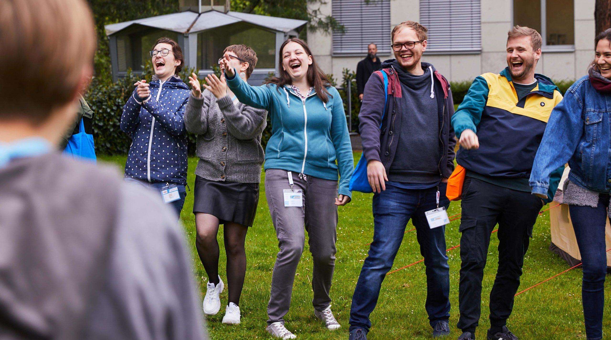 """Das Bild zeigt eine Projektmacherin der Projektgruppe """"Inklusion bei den Pfadfinder*innen"""" mit vier anderen Personen, die gemeinsam einen Energizer spielen. © Servicestelle Jugendbeteiligung, 2019"""