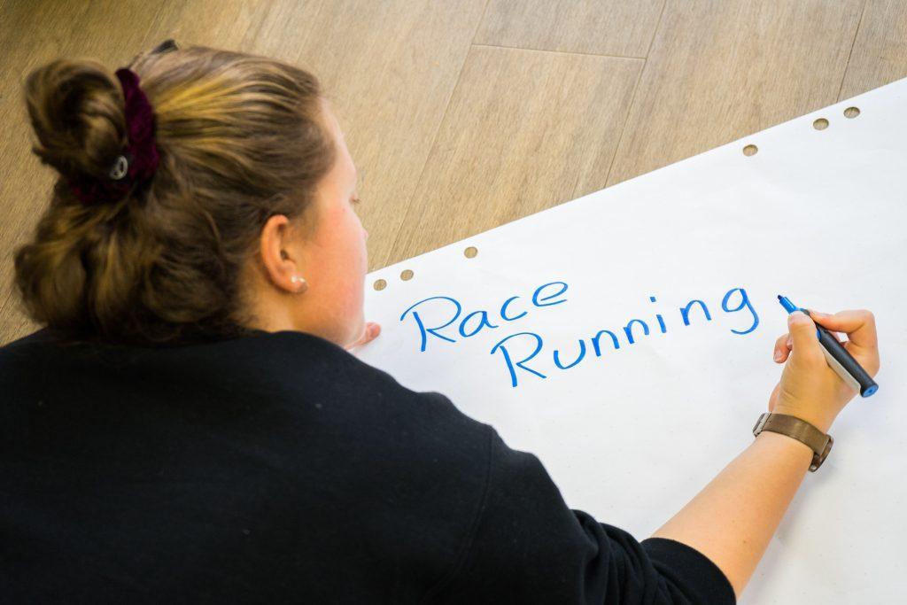 """Das Bild zeigt eine Projektmacherin des Projekts """"RaceRunning"""", die auf ein Blatt die Überschrift """"Race Running"""" schreibt. © Servicestelle Jugendbeteiligung e. V., 2019"""
