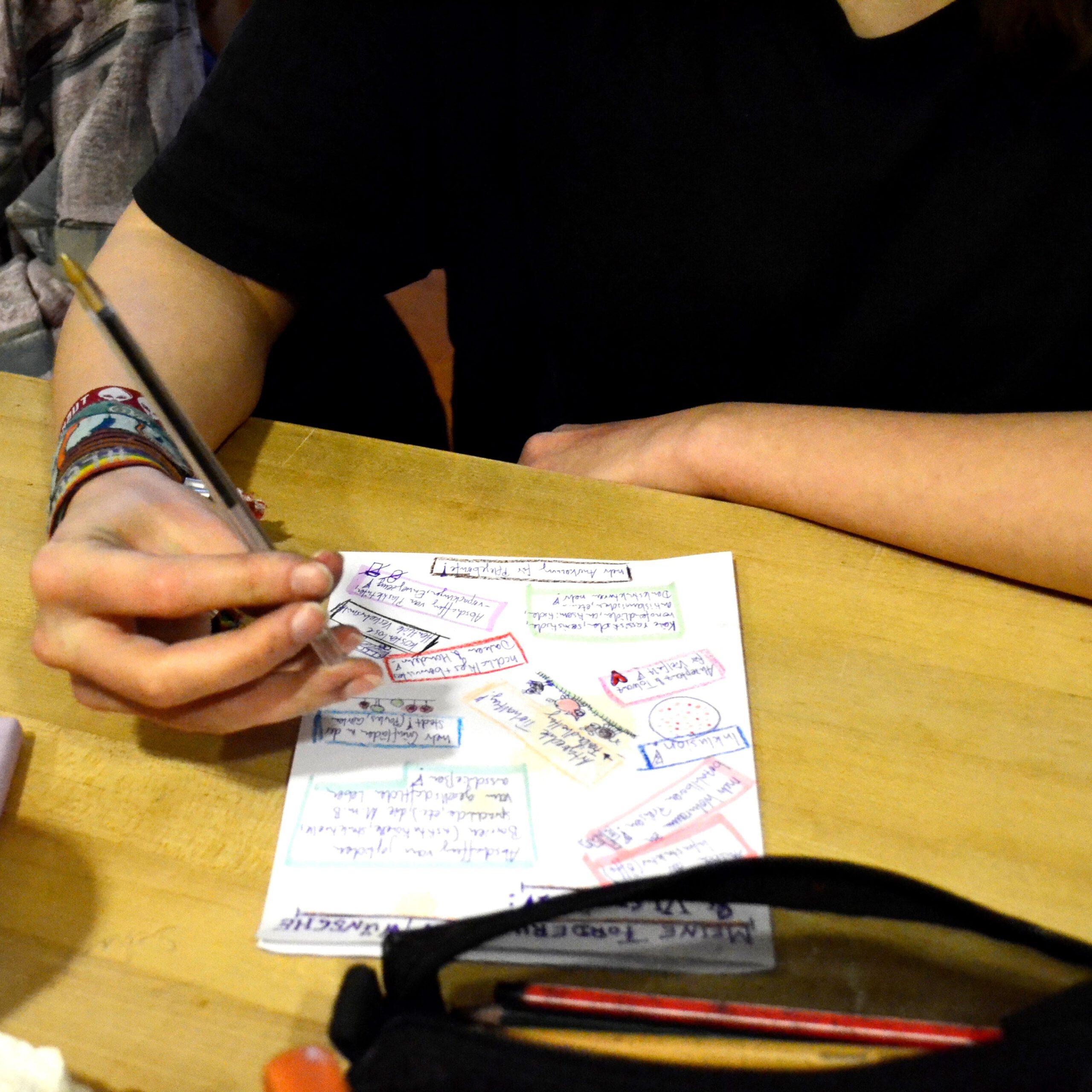 Auf dem Bild ist eine nicht vollständig zu sehende Person abgebildet. Die Person hält einen Stift in der Hand und zeichnet auf ein bemaltes Papier. Im Vordergrund liegt ein offenes Federmäppchen. © Servicestelle e.V., 2019