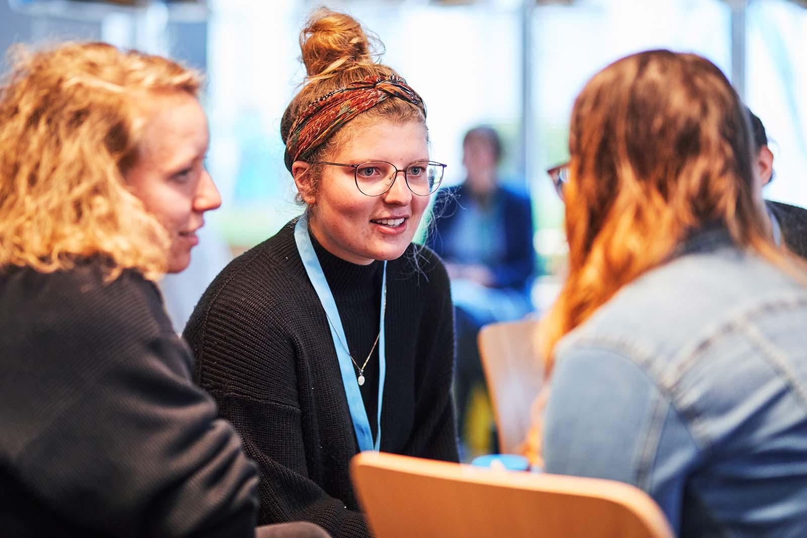 Drei Frauen, die sich miteinander unterhalten und dabei lächeln. © Aktion Mensch e. V. / Servicestelle Jugendbeteiligung e. V./Anna Spindelndreier, 2019