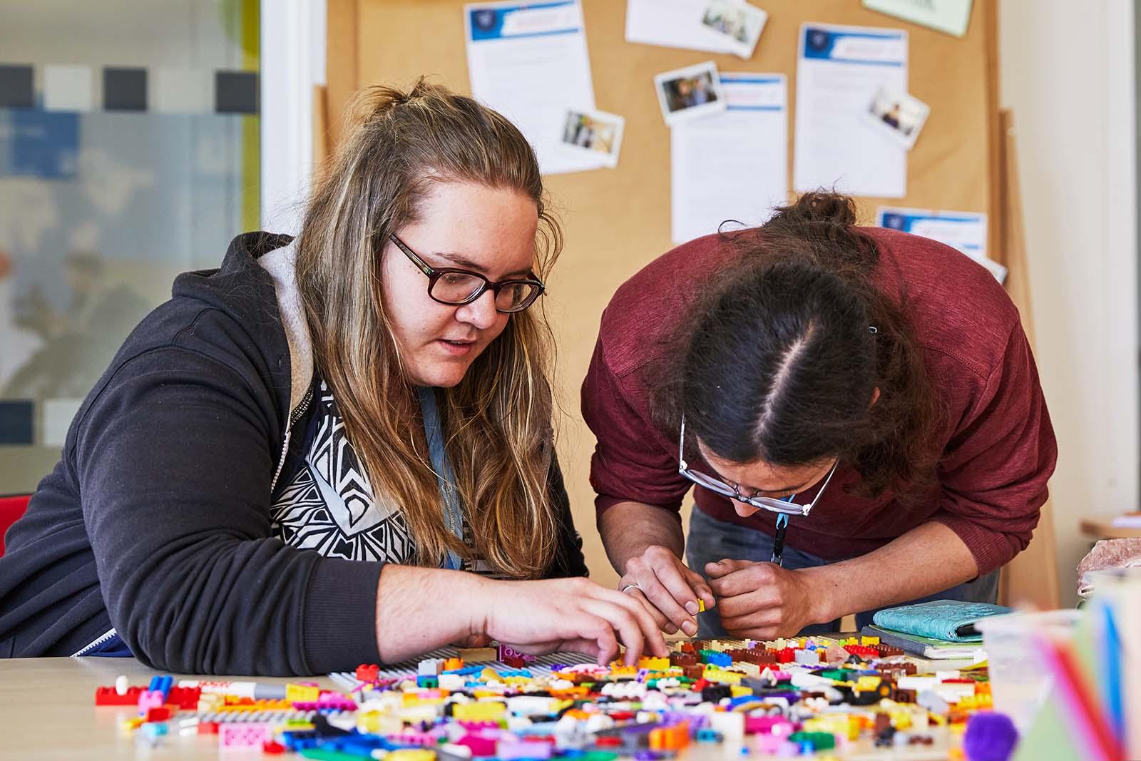 """Eine Frau und ein Mann bauen etwas aus bunten Legosteinen und unterhalten sich währenddessen. © Aktion Mensch e. V. / Servicestelle Jugendbeteiligung e. V./Anna Spindelndreier, 2019"""""""