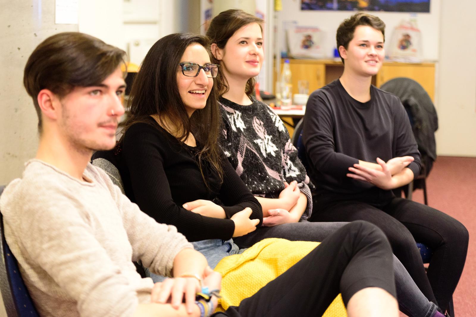 """Drei Frauen und ein Mann sitzen auf Stühlen und gebärden. © Servicestelle Jugendbeteiligung e. V./ Marius Klemm, 2018"""""""