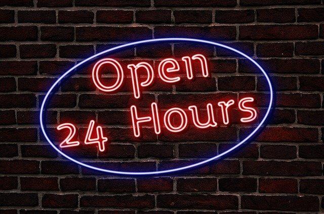 """Das Bild zeigt eine Backsteinwand mit einem Neonschild, auf dem steht: """"Open 24 Hours"""".© Servicestelle Jugendbeteiligung e. V., 2021"""